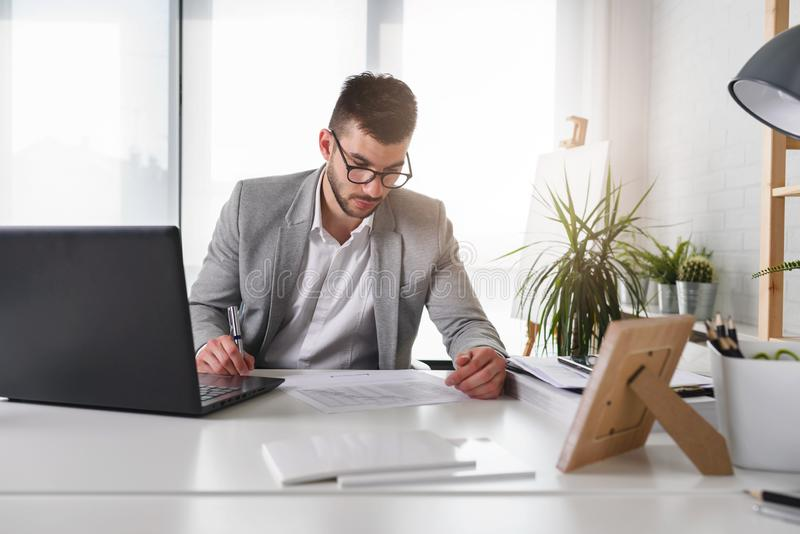 Hombre de negocios que se sienta en su escritorio de oficina E fotografía de archivo libre de regalías