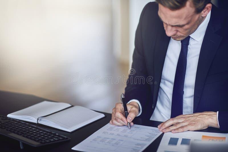 Hombre de negocios que se sienta en su escritorio de oficina que mira sobre documentos foto de archivo libre de regalías
