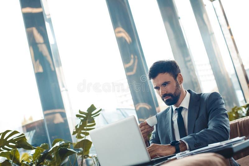Hombre de negocios que se sienta en un café express de consumición de trabajo del restaurante del centro de negocios concentrado fotos de archivo