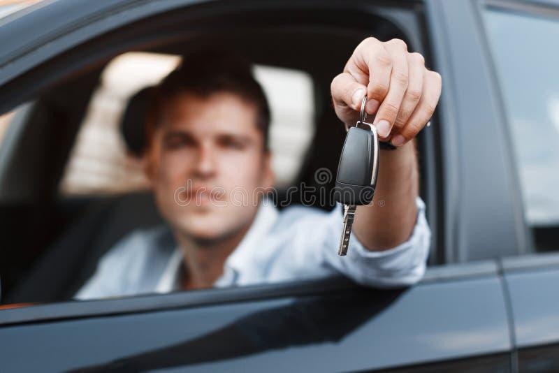 Hombre de negocios que se sienta en un coche y que da una llave del coche fotos de archivo libres de regalías