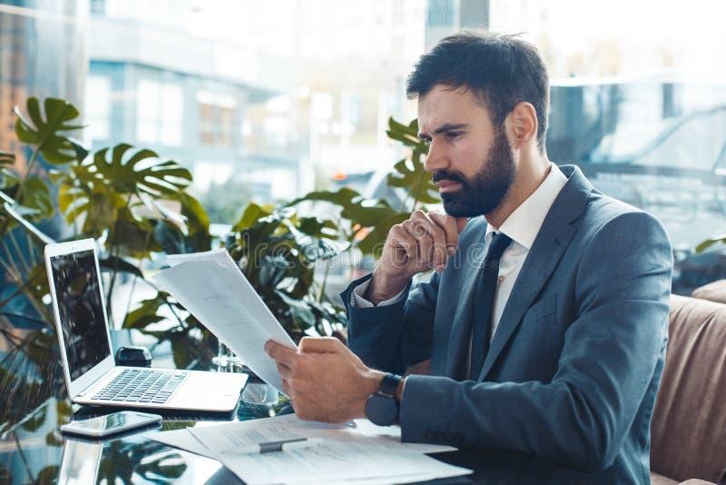 Hombre de negocios que se sienta en un contrato de la lectura del restaurante del centro de negocios concentrado fotos de archivo libres de regalías