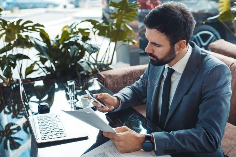 Hombre de negocios que se sienta en un contrato de la lectura del restaurante del centro de negocios que llama vista lateral fotografía de archivo
