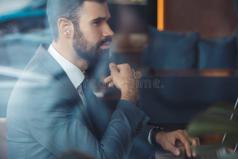 Hombre de negocios que se sienta en un restaurante del centro de negocios con el ordenador portátil pensativo foto de archivo libre de regalías