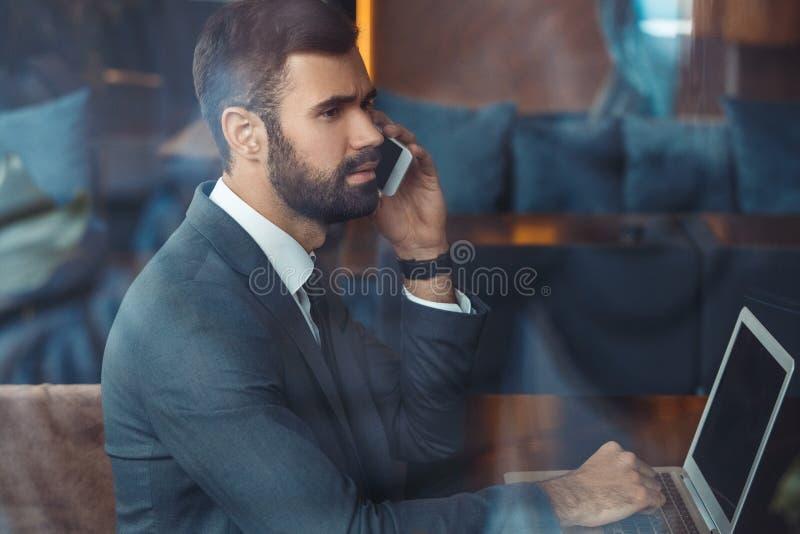 Hombre de negocios que se sienta en un restaurante del centro de negocios con llamada de teléfono del ordenador portátil imágenes de archivo libres de regalías