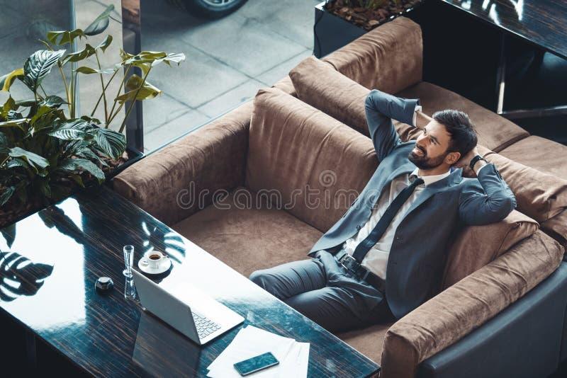 Hombre de negocios que se sienta en un resto del restaurante del centro de negocios en la opinión superior del sofá foto de archivo