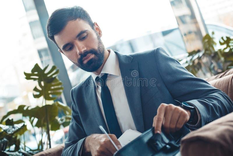 Hombre de negocios que se sienta en una comprobación de la cartera del restaurante del centro de negocios foto de archivo libre de regalías