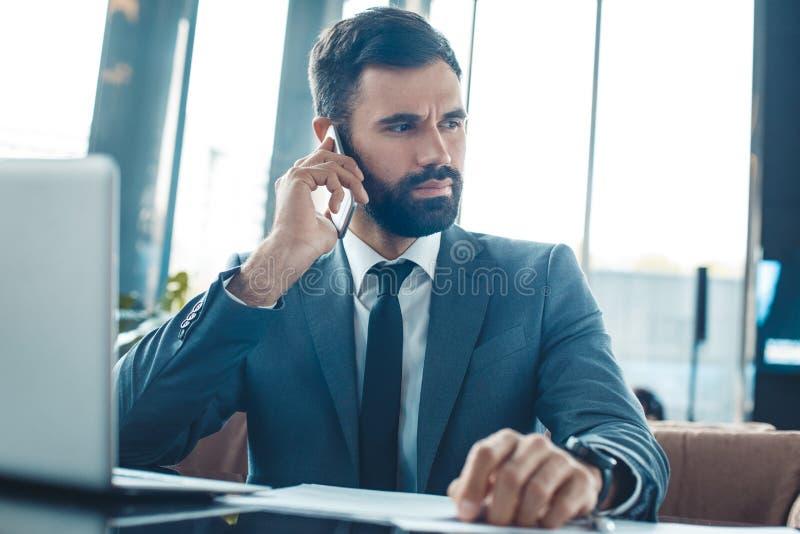 Hombre de negocios que se sienta en una comunicación del smartphone del restaurante del centro de negocios que escucha imagenes de archivo