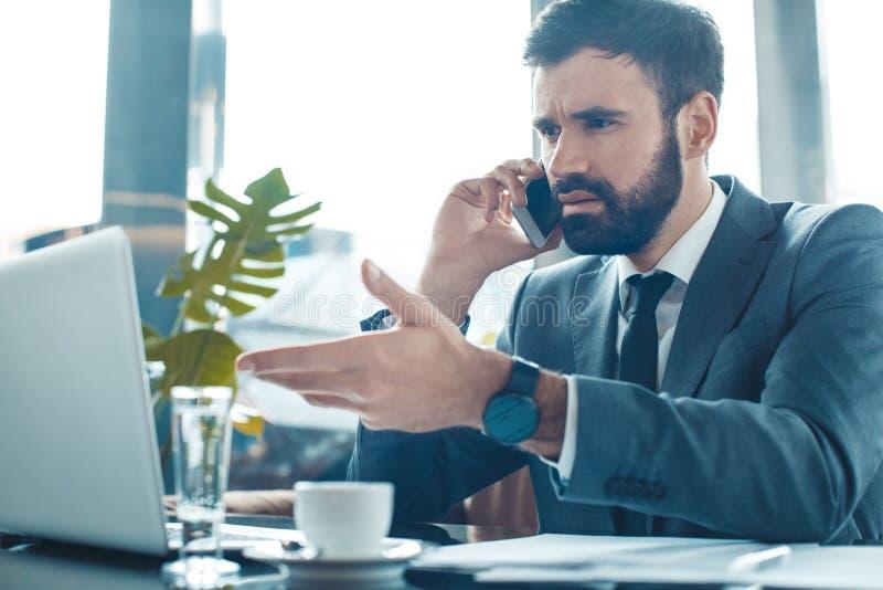 Hombre de negocios que se sienta en una comunicación del smartphone del restaurante del centro de negocios insatisfecha imagenes de archivo