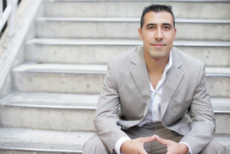Hombre de negocios que se sienta en una escalera imagenes de archivo