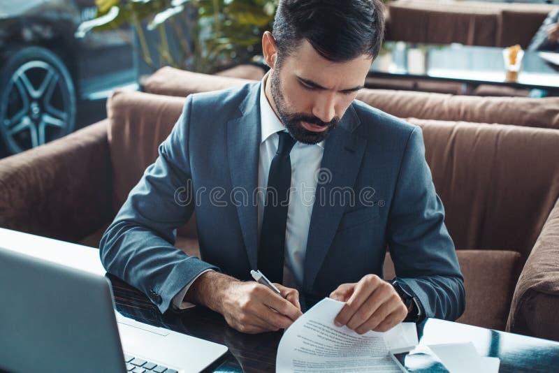 Hombre de negocios que se sienta en una opinión superior de firma del contrato del restaurante del centro de negocios fotografía de archivo