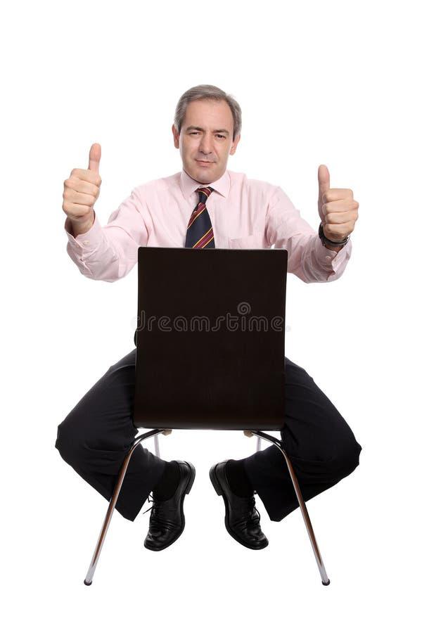 Hombre de negocios que se sienta en una silla fotografía de archivo libre de regalías
