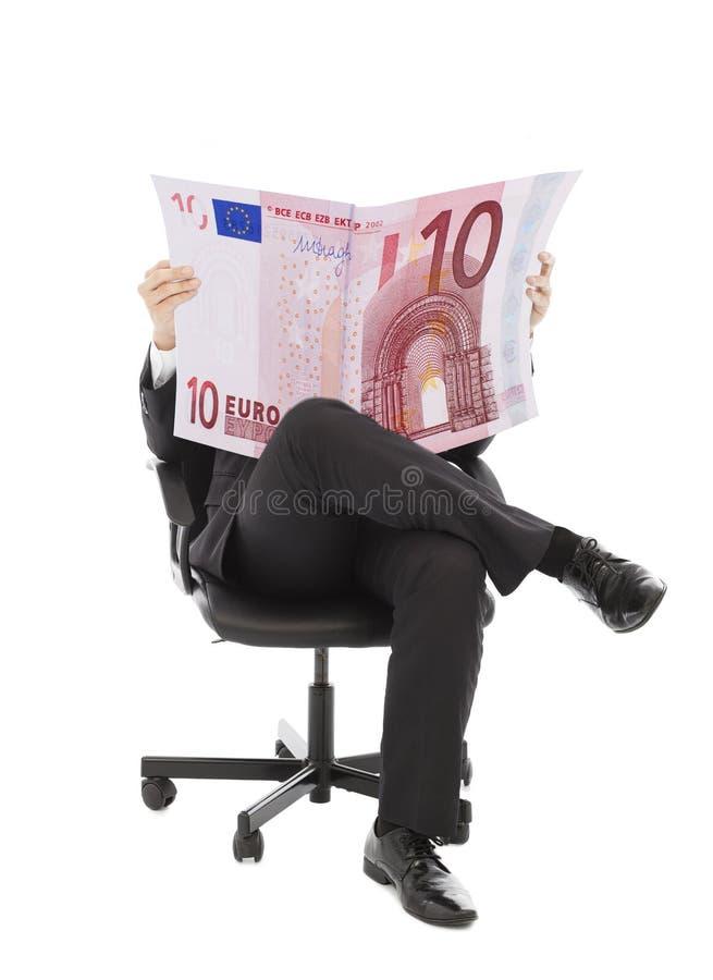 Hombre de negocios que se sienta en una silla con moneda euro imagenes de archivo
