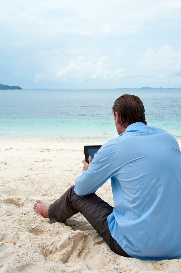 Hombre de negocios que se sienta y que trabaja en la playa imágenes de archivo libres de regalías