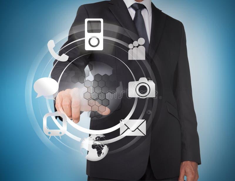 Hombre de negocios que selecciona iconos en un holograma imagen de archivo