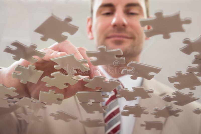 Hombre de negocios que separa rompecabezas fotografía de archivo libre de regalías