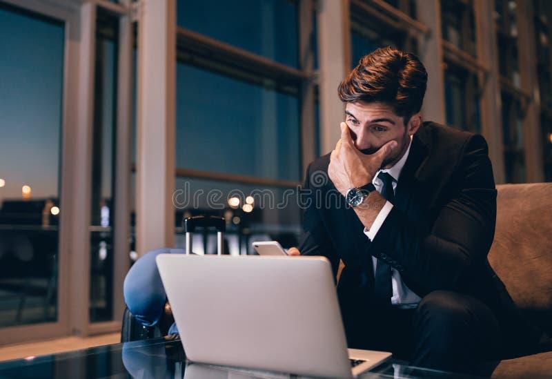 Hombre de negocios que siente cansado mientras que espera en el salón del aeropuerto imagen de archivo