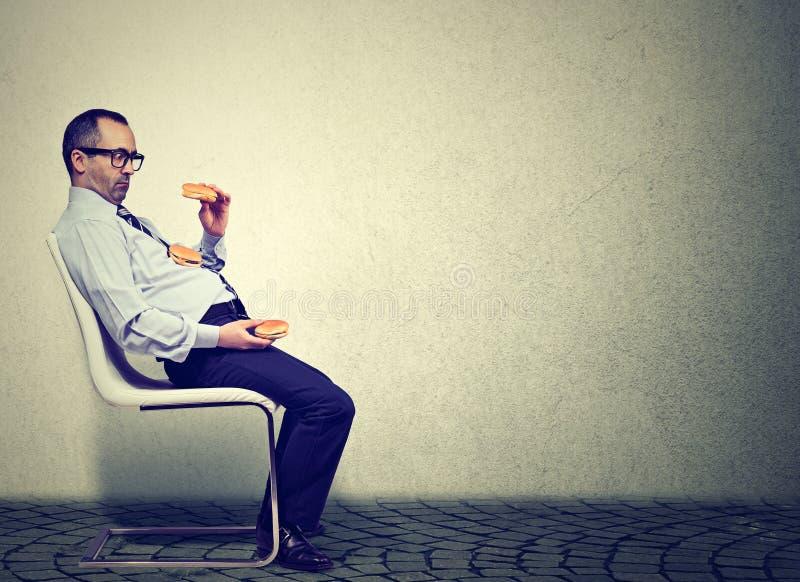 Hombre de negocios que siente cansado y soñoliento después de comer demasiadas hamburguesas para el almuerzo fotografía de archivo