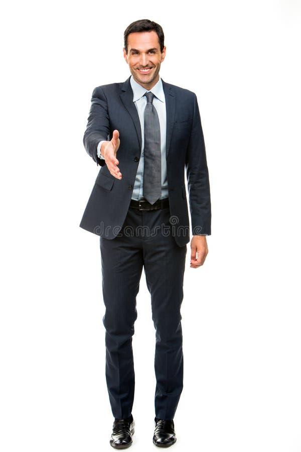 Hombre de negocios que sonríe aumentando su brazo para sacudir las manos foto de archivo libre de regalías