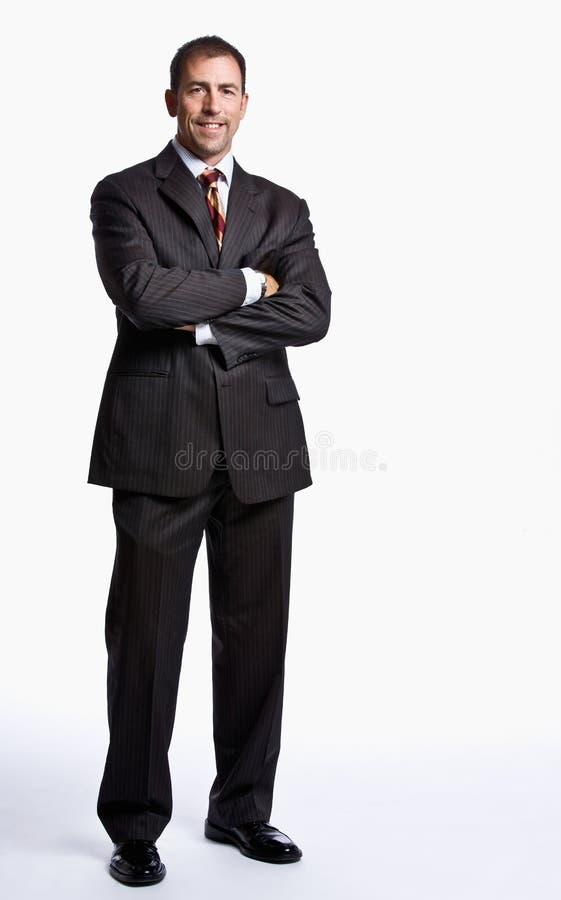 Hombre de negocios que sonríe con los brazos cruzados imagen de archivo libre de regalías