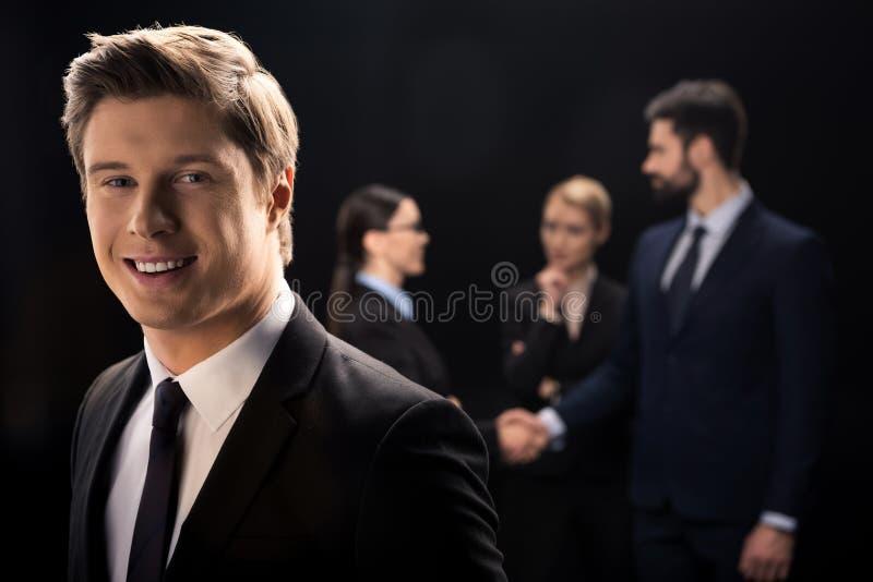 Hombre de negocios que sonríe en primero plano mientras que hombres de negocios que conectan detrás fotos de archivo libres de regalías