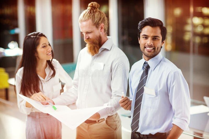 Hombre de negocios que sonríe mientras que colegas que discuten sobre modelo stock de ilustración