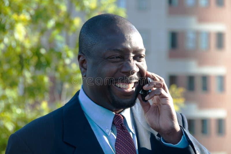 Hombre de negocios que sonríe y que habla en el teléfono celular fotografía de archivo libre de regalías