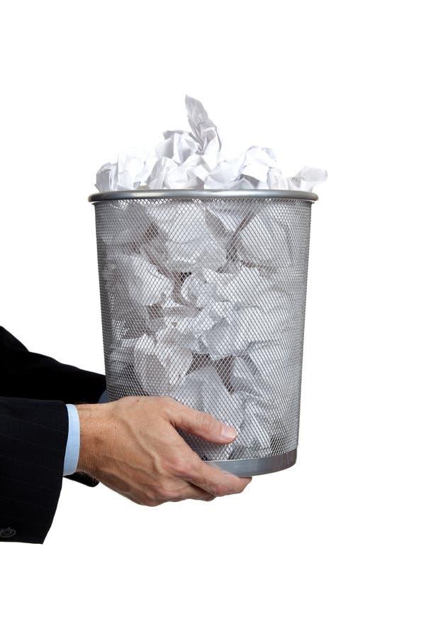 Hombre de negocios que sostiene el bote de basura lleno imagen de archivo