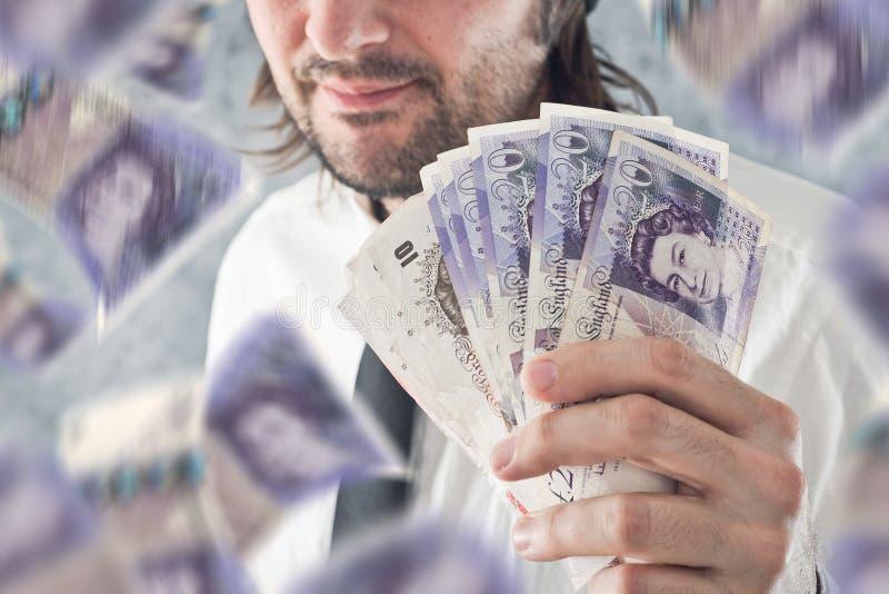 Hombre de negocios que sostiene el dinero de las libras británicas, bnknotes que caen de imagen de archivo libre de regalías