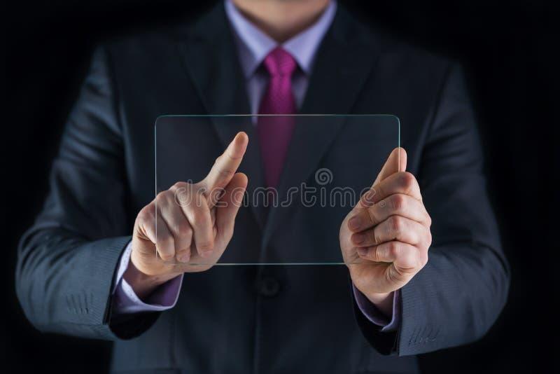 Hombre de negocios que sostiene el móvil transparente futurista en blanco, elegante fotos de archivo