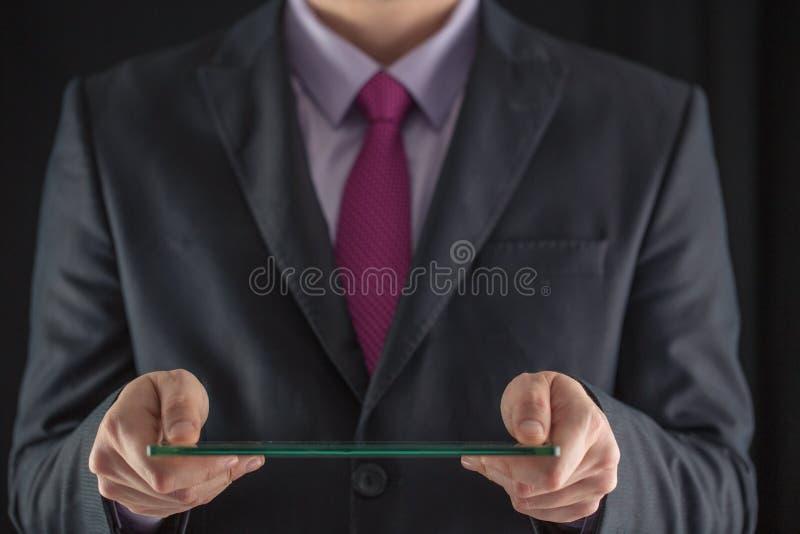 Hombre de negocios que sostiene el móvil transparente futurista en blanco, elegante foto de archivo libre de regalías