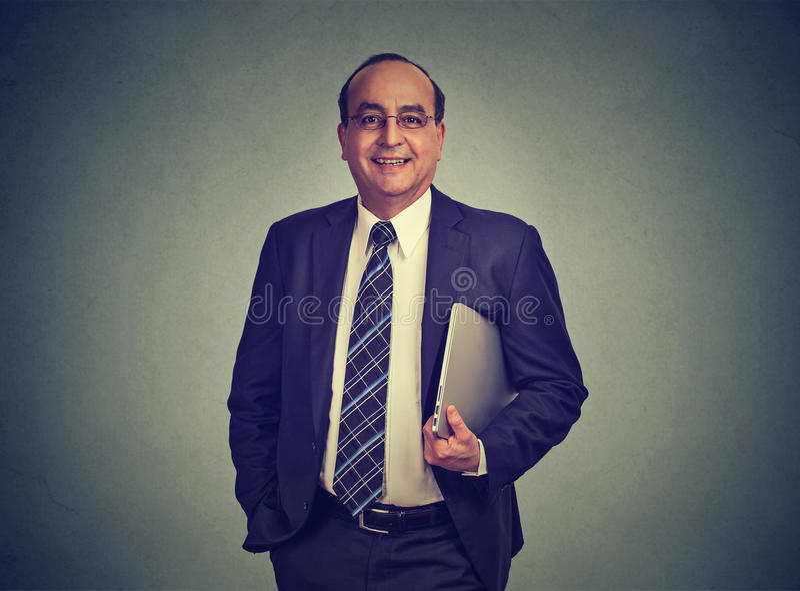 Hombre de negocios que sostiene el ordenador portátil en su mano imagen de archivo libre de regalías