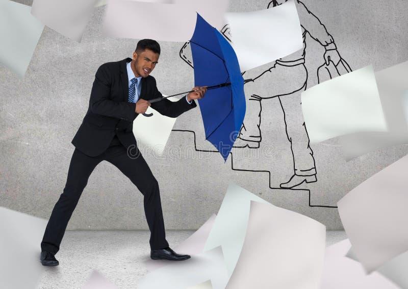 Hombre de negocios que sostiene el paraguas azul en medio de los papeles del vuelo contra la pared de la pintada fotografía de archivo