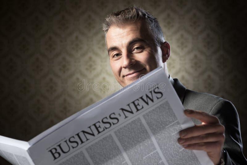 Hombre de negocios que sostiene el periódico imagenes de archivo