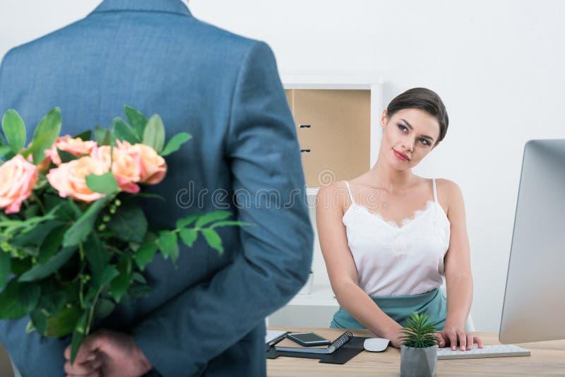 Hombre de negocios que sostiene el ramo de rosas para su colega que se sienta en el lugar de trabajo fotografía de archivo