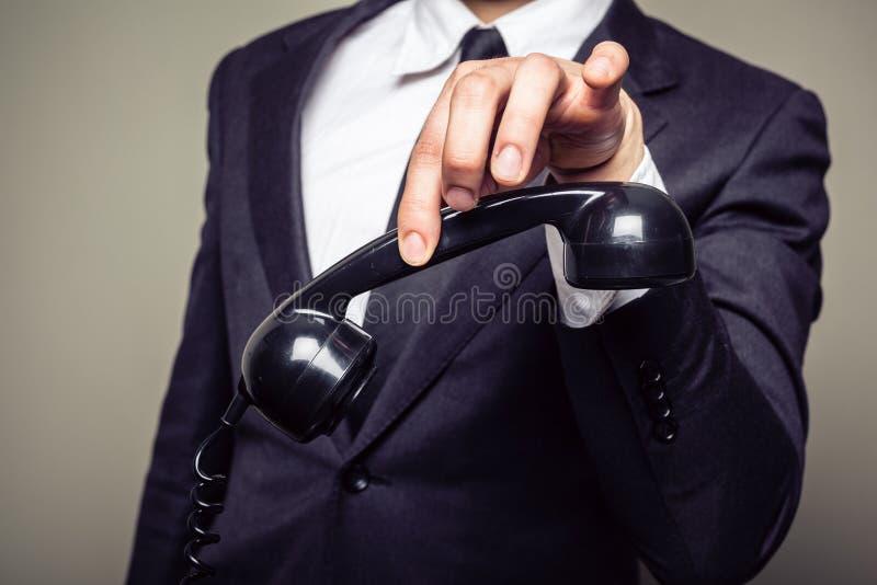 Hombre de negocios que sostiene el teléfono con sus fingeres imagenes de archivo