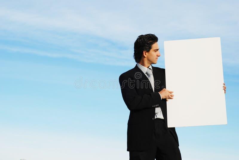 Hombre de negocios que sostiene el verraco en blanco fotografía de archivo