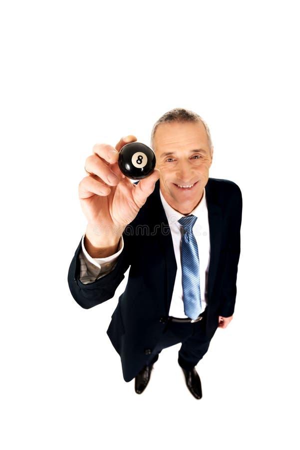 Hombre de negocios que sostiene la bola de billar negra foto de archivo