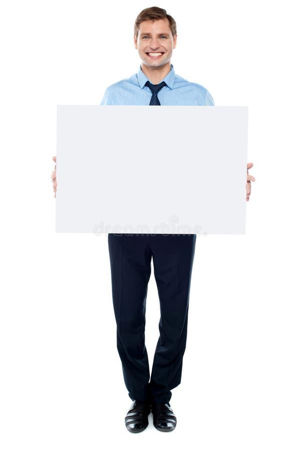 Hombre de negocios que sostiene la cartelera blanca en blanco imagenes de archivo