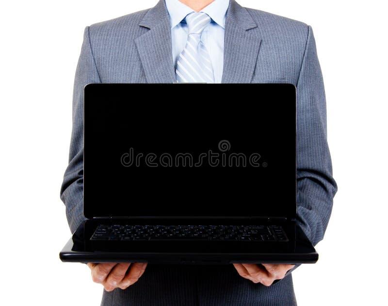 Hombre de negocios que sostiene la computadora portátil en blanco fotografía de archivo libre de regalías