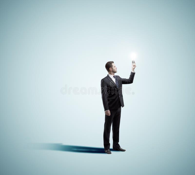 Hombre de negocios que sostiene la lámpara imagen de archivo