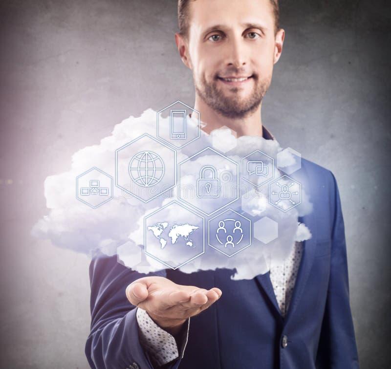 Hombre de negocios que sostiene la nube con diversos iconos digitales fotos de archivo