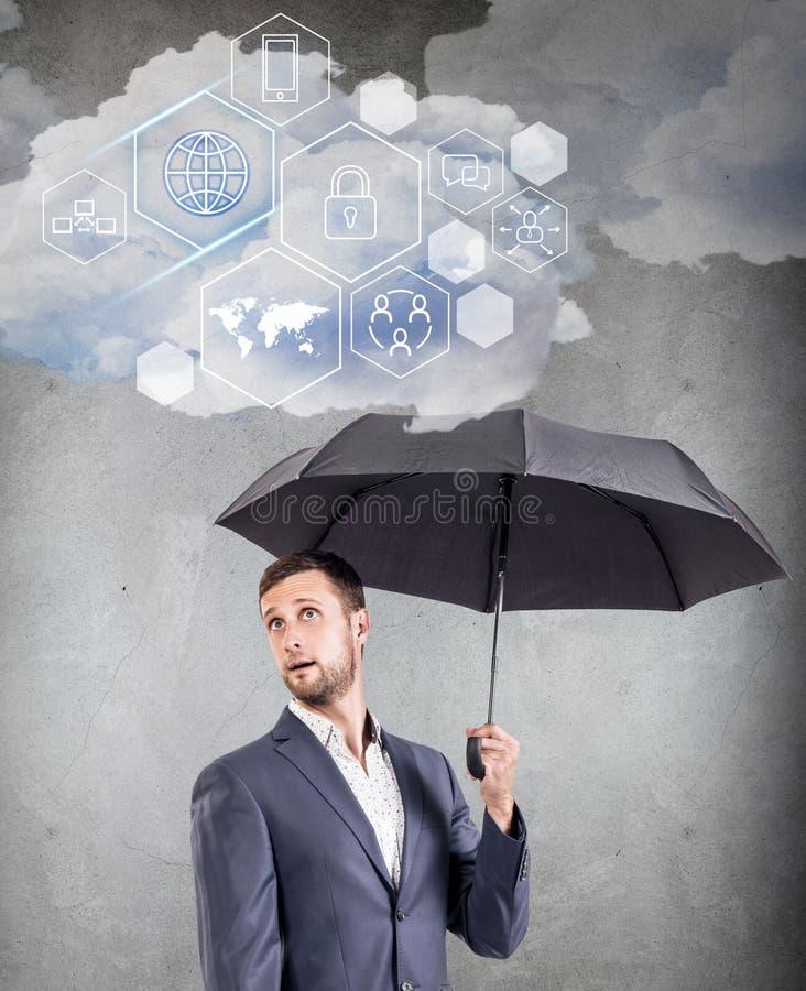 Hombre de negocios que sostiene la nube con diversos iconos digitales fotos de archivo libres de regalías