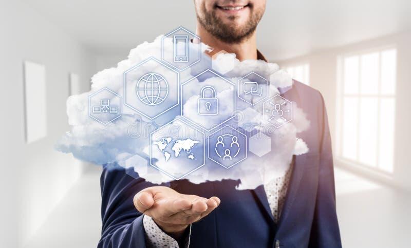 Hombre de negocios que sostiene la nube con diversos iconos digitales imágenes de archivo libres de regalías