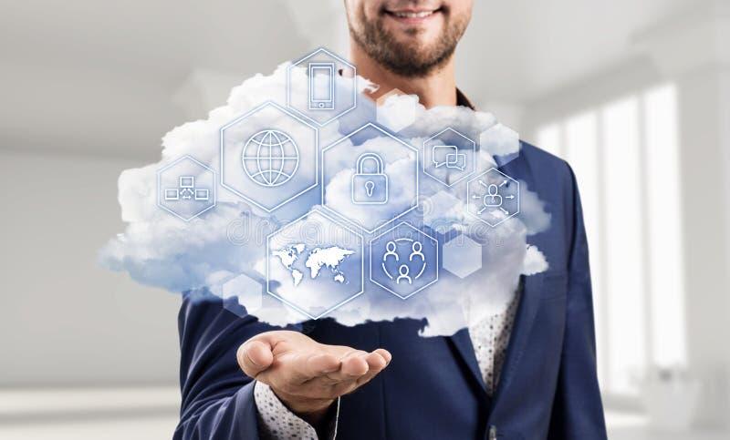 Hombre de negocios que sostiene la nube con diversos iconos digitales fotografía de archivo
