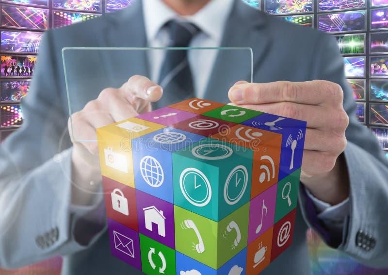 Hombre de negocios que sostiene la pantalla de cristal con los apps con representaciones visuales coloridas de las pantallas foto de archivo