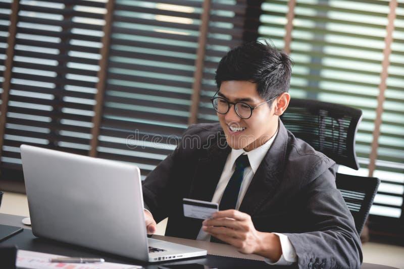 Hombre de negocios que sostiene la tarjeta de crédito que hace compras en línea, haciendo la transacción foto de archivo libre de regalías