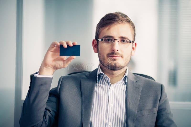 Hombre de negocios que sostiene la tarjeta de visita vacía en la oficina imágenes de archivo libres de regalías