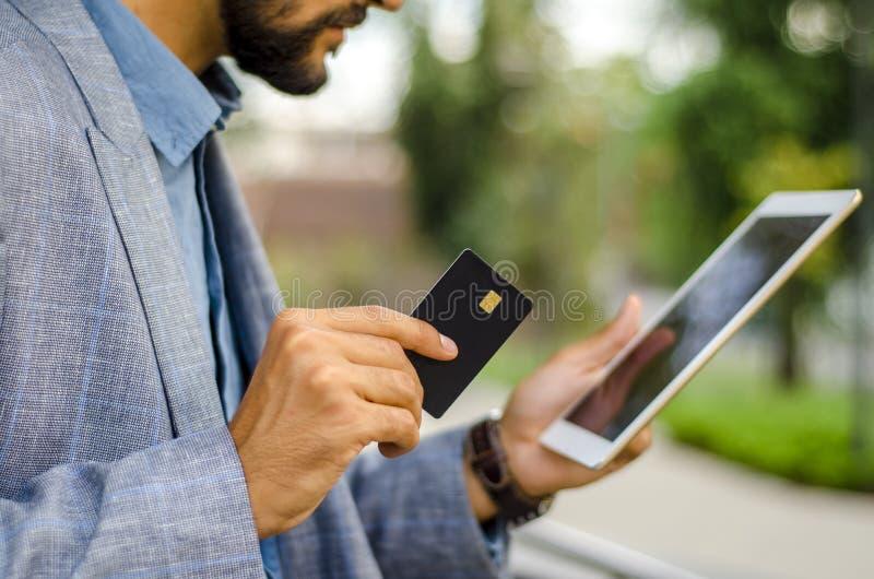 Hombre de negocios que sostiene la tarjeta y la tableta vacías negras de crédito foto de archivo
