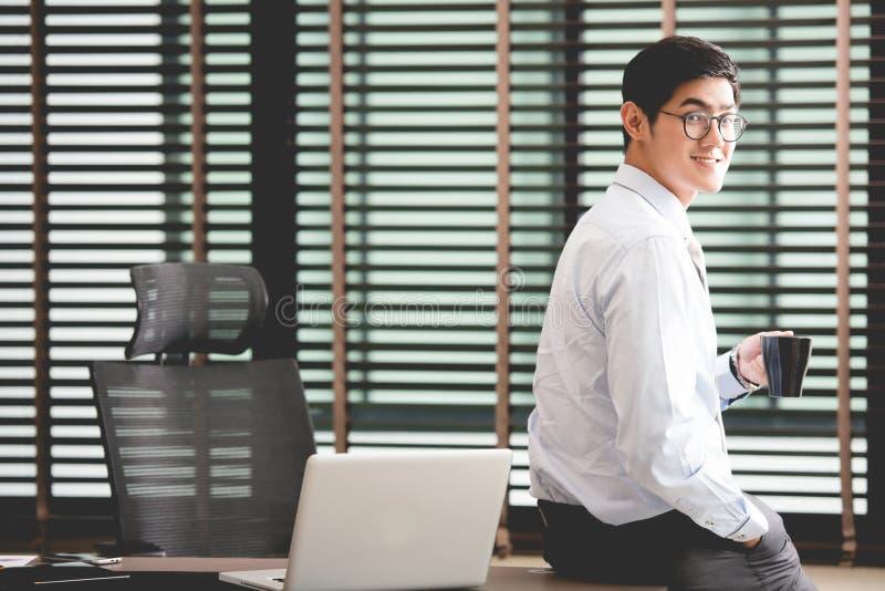 Hombre de negocios que sostiene la taza de café que se sienta en el escritorio en oficina imágenes de archivo libres de regalías