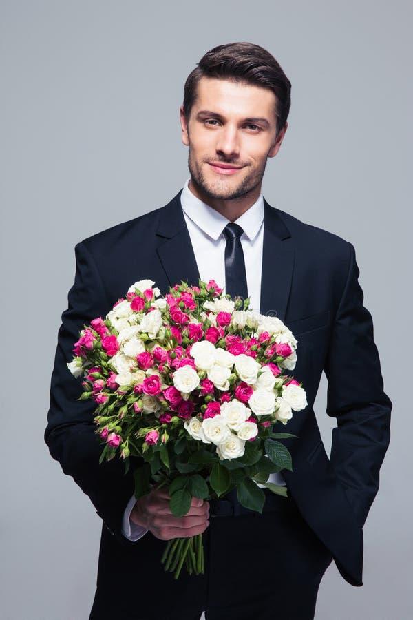 Hombre de negocios que sostiene las flores imágenes de archivo libres de regalías